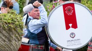 A pipe band bass drummer plays his instrument on parade