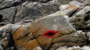 Painted lips on a rock on the coast