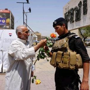 बगदाद में तहरीर चौके के पास एक सैनिक को फूल देता एक व्यक्ति