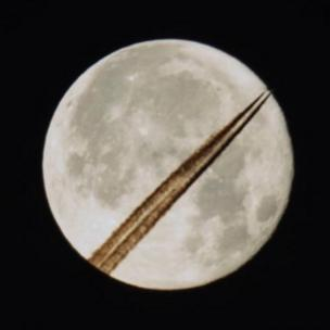 The supermoon appears with trails from an aircraft juxtaposed against it
