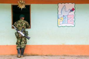 A Farc guerrilla fighter peers through a store window in Santa Lucia, July 2016