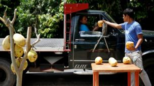 Josue Moreno, 19, gives a coconut to a customer at his street stall in La Fria, Venezuela.