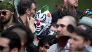 A man in a clown face stands in the midst of the protest
