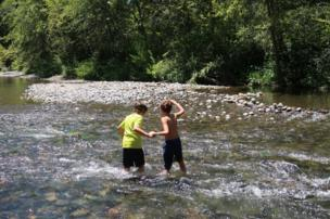Two children play in a a creek