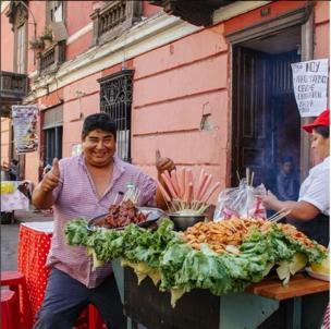 hombre saluda al lado de un negocio de comida callejera