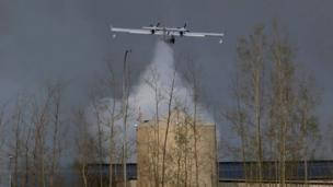 A plane dumps water on the wildfires near Fort McMurray, Alberta (07 May 2016)