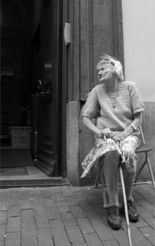 An elderly lady sits outside her doorway