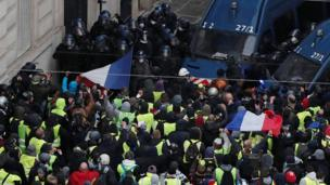 Hundreds of protesters surge towards a line of police officers in Paris