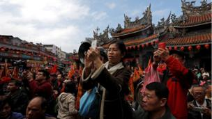 People take photos of the decorated carcasses of the sacrificial pigs, in Sanxia district, New Taipei City, Taiwan, 2 February 2017.