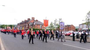 Large group carrying flags and banners march through Ardoyne peacefully