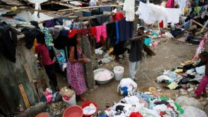 People wash their clothes in front of their partially destroyed houses after Hurricane Matthew passes Jeremie in Haiti
