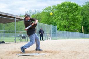 A man swings for a baseball
