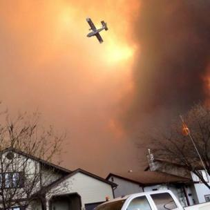 Smoke fills the air as a small plane flies overhead in Fort McMurray, Alberta