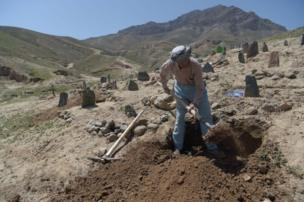 An Afghan man digs a grave for one of the victims of a suicide attack this year that killed nearly 60 people including children