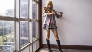 Cosplayer playing a violin, wearing a Japanese schoolgirl costume