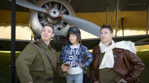 Two serving RAF officers dressed as First World War pilots entertain a youngster.