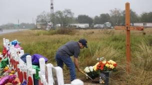 San Antonio resident, Rey Flores digs up sand to place flowers next to a cross left for a memorial to the 26 people who died
