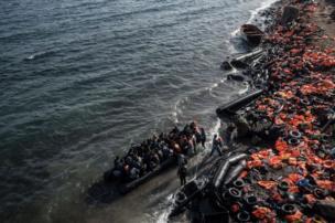 Chalecos salvavidas abandonados en la playa mientras otra balsa con gente llega a la costa