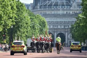 Police escort members of the Household Cavalry along the Mall in central London.