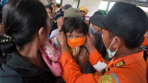 An officer with the disaster management agency BPBD places a mask on child at a shelter