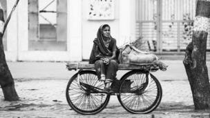 A woman sitting on a car in an Agra city street