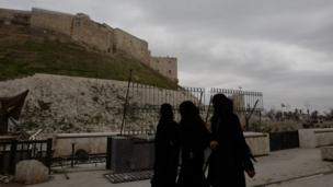 Three women dressed in the niqab walk in front of the citadel in Aleppo