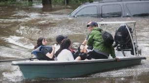 Volunteers and officers from a Houston neighbourhood security patrol help rescue residents in River Oaks (27 August 2017)