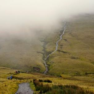 Walkers head into the clouds on the path towards Corn Du in the Brecon Beacons