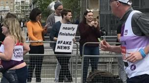 Photo of a spectator holding up a sign which says 'nearly finished #FAKENEWS'