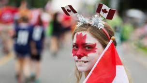 "Clara Swain looks on with a painted face as she participates in the East York Toronto Canada Day parade, as the country marks its 150th anniversary with ""Canada 150"" celebrations, in Toronto, Ontario"
