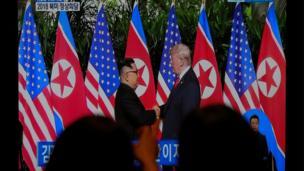 رهگذران در خیابانی در نیویورک، لحظه دیدار رهبران آمریکا و کره شمالی را تماشا میکنند. این دیدار و مذاکرات، در داخل آمریکا هم خبرساز بوده است.