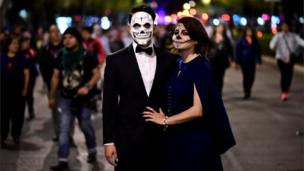 A couple pose for a photo during the Catrinas parade in Mexico City.