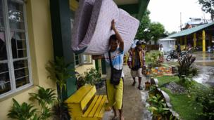 A resident carries a matress inside a classroom used as an evacuation centre as Typhoon Mangkhut approached the city of Tuguegarao