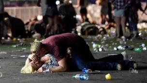 Hombre protege a una mujer en el suelo tras el ataque.
