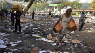 People carry merchandise from the Delimart supermarket complex which was burned during two days of protests against a planned hike in fuel prices in Port-au-Prince, Haiti, Sunday, July 8, 2018.