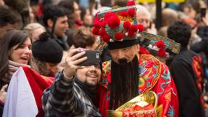 A man takes a selfie with a performer during the Chinese New Year parade in London