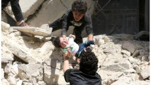Syrians evacuate a toddler from a destroyed building following a reported air strike on the rebel-held neighbourhood of al-Kalasa in the northern Syrian city of Aleppo, on April 28, 2016.