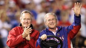 George W Bush and his father George HW Bush wave to the crowd before the Texas Rangers host the San Francisco Giants in Game Four of the 2010 MLB World Series at Rangers Ballpark in Arlington on October 31, 2010 in Arlington, Texas.