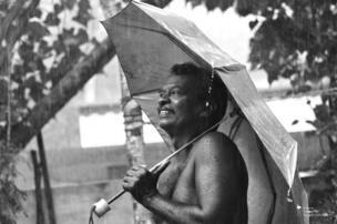Un hombre con un paraguas y una sonrisa bajo la lluvia.