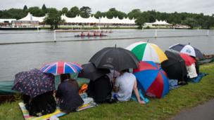 Visitors shelter under umbrellas as they watch the rowing from the bank of the Thames during day one of the Henley Royal Regatta.