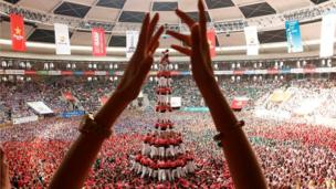 "Colla Vella Xiquets de Valls form a human tower called ""castell"", while a supporter applauds, during a biannual competition in Tarragona city, Spain, October 2, 2016."