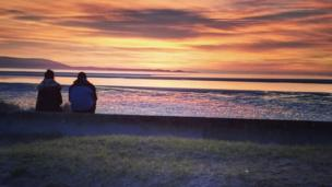 A couple watching the sunset in Llanelli