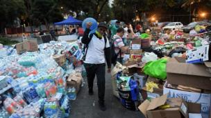 A man walks through piles of food and water bottles