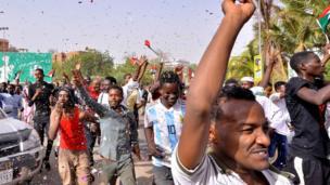 """سودانيون يرددون شعارات فور سماع إعلان وزير الدفاع """"اقتلاع النظام"""" و""""التحفظ"""" على البشير."""