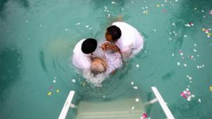 An elderly woman is baptised during the annual gathering of the La Luz del Mundo church in Guadalajara