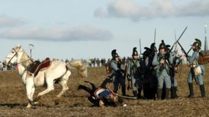 A history enthusiast dressed in regimental costume falls off his horse during the re-enactment