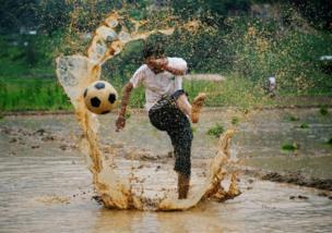 Seorang pria menendang bola dalam acara yang merayakan Asar Pandra, juga disebut Hari Padi Nasional, di Lalitpur, Nepal.