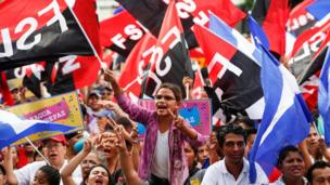 Supporters of the president wave his party's flags and carry well-designed professionally-printed signs - a stark contrast to the images of the protests
