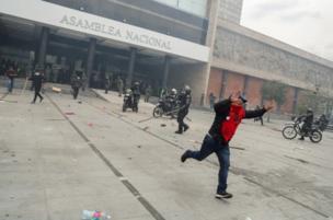 Un hombre corre mientras policías despejan la Asamblea Nacional