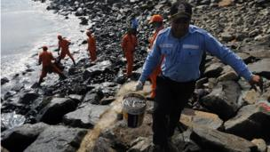 Members of the Pollution Response Team remove black oil washed ashore